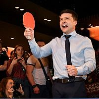 Ukrainian comic actor, showman and presidential frontrunner Volodymyr Zelensky surrounded by cameramen and photographers plays table tennis with a journalist ahead of the provisional results at the headquarter in Kiev, on March 31, 2019. (Genya SAVILOV/AFP)
