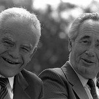 Flashback to the rotation era: Then-prime minister Yitzhak Shamir (left) and then-foreign minister Shimon Peres enjoy each other's company during a Mimouna celebration at Sacher Park in Jerusalem, March 15, 1988. (Nati Harnik / Government Press Office)