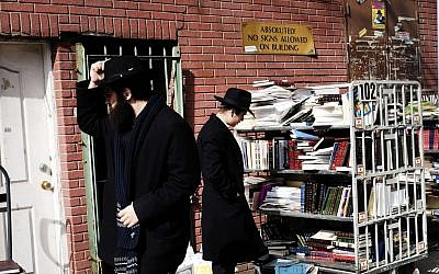 Illustrative: Ultra-Orthodox Jewish men look through books in the neighborhood of Crown Heights on February 25, 2019 in New York City (Spencer Platt/Getty Images via JTA)