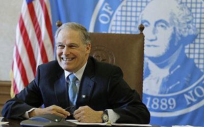 In this Wednesday, Feb. 27, 2019 photo, Washington Gov. Jay Inslee sits in front of the state seal as he takes part in a conference call meeting with members of the AARP, at the Capitol in Olympia, Wash. (AP Photo/Ted S. Warren)