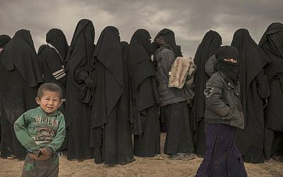 Women and children stand in line at a reception area for people evacuated from the last shred of territory held by Islamic State militants, outside Baghouz, Syria, on March 6, 2019. (AP/Gabriel Chaim)