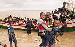 In this photo supplied by the Red Cross Red Crescent Climate Center, survivors of Cyclone Idai arrive by rescue boat in Beira, Mozambique, March 21, 2019. (Denis Onyodi - Red Cross Red Crescent Climate Center via AP)