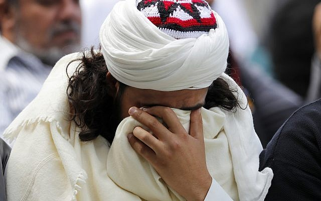 A Muslim man reacts during Friday prayers at Hagley Park in Christchurch, New Zealand, March 22, 2019. (AP Photo/Vincent Thian)
