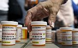 In this photo from August 17, 2018, family and friends who have lost loved ones to OxyContin and opioid overdoses leave pill bottles in protest outside the headquarters of Purdue Pharma, which is owned by the Sackler family, in Stamford, Connecticut. (AP Photo/Jessica Hill, File)