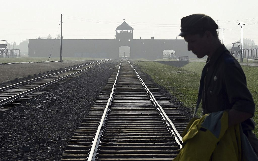A man crosses the iconic rails leading to the former Nazi death camp of Auschwitz-Birkenau in Poland, July 29, 2016. (AP Photo/Alik Keplicz, FILE)