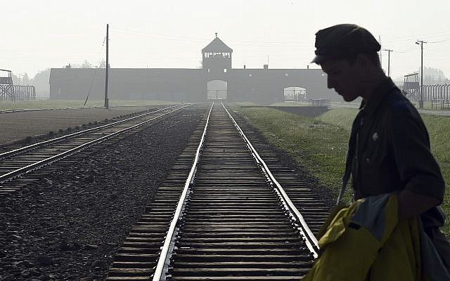 In this file photo from July 29, 2016, a man crosses the iconic rails leading to the former Nazi death camp of Auschwitz-Birkenau in Poland. (AP Photo/Alik Keplicz, FILE)