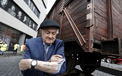 Holocaust survivor Leon Kaner, age 94, shows his tattoo number as he stands beside a vintage German train car, like those used to transport people to Auschwitz and other death camps, outside the Museum of Jewish Heritage, in New York on March 31, 2019. (AP Photo/Richard Drew)