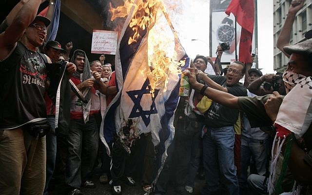 Demonstrators burn an Israeli flag during a protest outside Israel's embassy in Caracas, Thursday, January 8, 2009. Protesters condemning Israel's offensive in the Gaza Strip sprayed graffiti and hurled shoes at the country's embassy in Venezuela on Thursday, backing President Hugo Chavez's decision to expel the Israeli ambassador. (AP Photo/Fernando Llano)