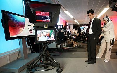 In this June 26, 2009 file photo BBC Persian service presenter Fardad Farahzad, right, gets ready to present the news, at the corporation's London headquarters  Inside the studios of BBC Persian television, dozens of journalists have been working around the clock at their computers and telephones, trying to report the news to Iran or, according to the government in Tehran, stirring up trouble. (AP Photo/Simon Dawson,file)
