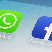 This file photo from February 19, 2014, shows WhatsApp and Facebook app icons on a smartphone in New York. (AP Photo/Patrick Sison, File)