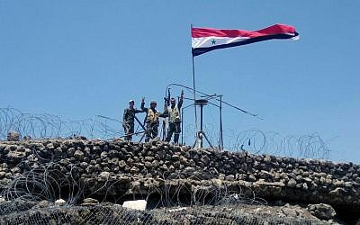 Illustrative: Syrian troops flash the victory sign next to the Syrian flag in Tel al-Haara, the highest hill in the southwestern Daraa province, Syria, July 17, 2018. (SANA via AP)