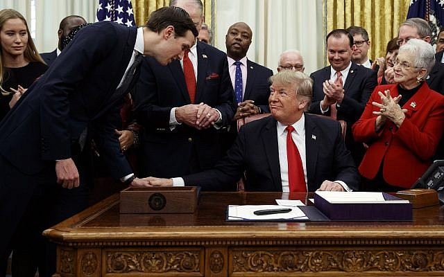 White House senior adviser Jared Kushner, left, talks with US President Donald Trump, seated, during a signing ceremony for criminal justice reform legislation in the Oval Office of the White House, in Washington, December 21, 2018. (Evan Vucci/AP)