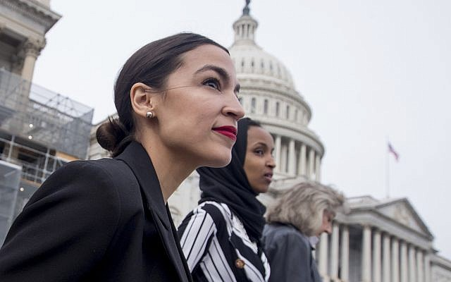 Democratic Represetnative Alexandria Ocasio-Cortez of New York, left, and Democratic Representative Ilhan Omar of Minnesota, center, walk down the House steps to take a group photograph of the House Democratic women members of the 116th Congress on the East Front Capitol Plaza on Capitol Hill in Washington, January 4, 2019, as the 116th Congress began. (AP Photo/Andrew Harnik)
