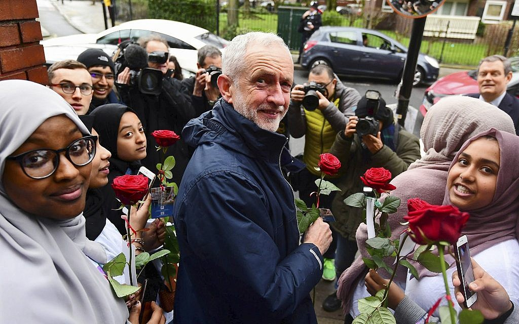 Britain's main opposition Labour Party leader Jeremy Corbyn is presented with flowers at the Finsbury Park Mosque in north London, during his visit on the annual Mosque open day, Sunday March 3, 2019. British police detained a man after Corbyn was hit by an egg during his visit to the Mosque Sunday, and the man charged with assault is due to appear in court Tuesday. (Victoria Jones/PA via AP)