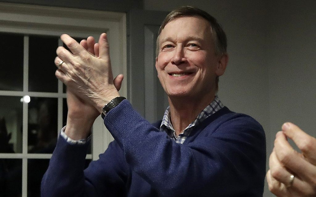 In this Feb. 13, 2019, file photo, former Colorado Gov. John Hickenlooper, left, applauds at a campaign house party, in Manchester, N.H. Hickenlooper is running for president, becoming the second governor to jump into the sprawling Democratic 2020 contest. Hickenlooper is a former brewpub owner and Denver mayor who hopes his two terms governing a swing state shows that he can unite the country. (AP Photo/Elise Amendola, File)