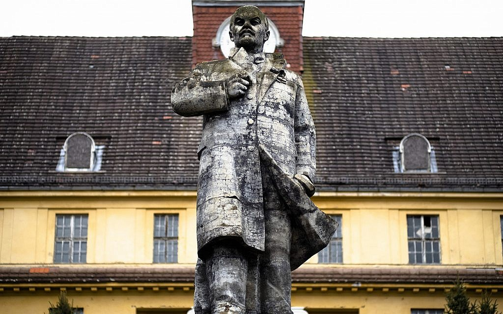"""In this Tuesday, Feb. 22, 2019 photo, a Lenin monument stands in front of the abandoned """"Haus der Offiziere"""", the headquarters for the Soviets' military high command in former East Germany, at the Wuensdorf neighborhood of Zossen, some 40 kilometers (25 miles) south of Berlin. (AP/Markus Schreiber)"""