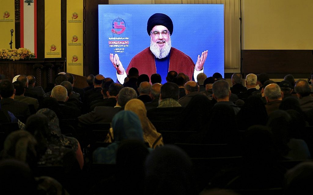 Supporters of the Iranian-backed Hezbollah terror group listen to a speech by Hezbollah leader Hassan Nasrallah via a video link in a southern suburb of Beirut, Lebanon, March 8, 2019. (AP Photo/Bilal Hussein)