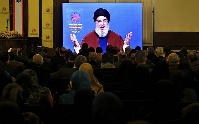Supporters of the Iranian-backed Hezbollah group listen to a speech of Hezbollah leader Sayyed Hassan Nasrallah, via a video link, in a southern suburb of Beirut, Lebanon, March 8, 2019. (AP Photo/Bilal Hussein)