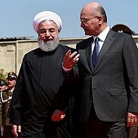 Iraqi President Barham Salih, right, walks with visiting Iranian President Hassan Rouhani, after inspecting an honor guard at Salam Palace, Baghdad, March 11, 2019. (AP Photo/Khalid Mohammed)