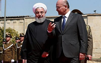 Iraqi President Barham Salih, right, walks with visiting Iranian President Hassan Rouhani, after inspecting an honor guard at Salam Palace, Baghdad, March 11, 2019. (AP/Khalid Mohammed)