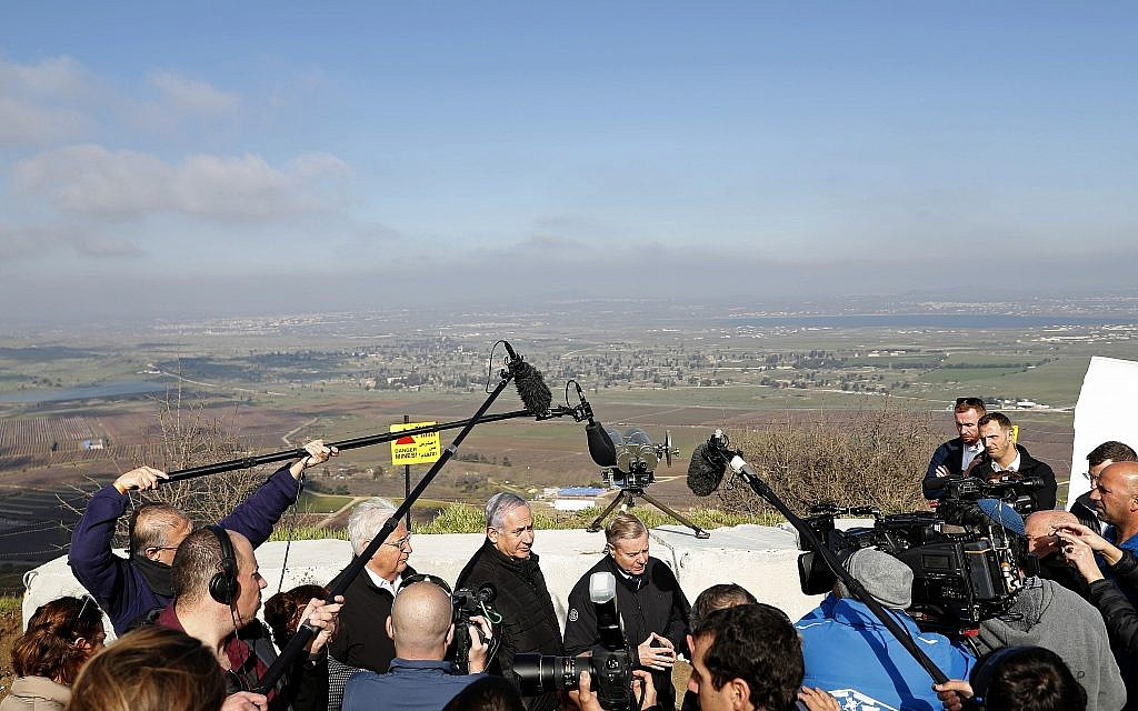 Israeli Prime Minister Benjamin Netanyahu, center, Republican US Senator Lindsey Graham, right, and US Ambassador to Israel David Friedman visit the border between Israel and Syria at the Golan Heights, Monday, March 11, 2019. (Ronen Zvulun/Pool via AP)