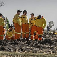 Members of Israels Zaka rescue and recovery team Israel examine wreckage at the scene where the Ethiopian Airlines Boeing 737 Max 8 crashed shortly after takeoff on Sunday killing all 157 on board, near Bishoftu, or Debre Zeit, south of Addis Ababa, in Ethiopia Tuesday, March 12, 2019. (AP Photo/Mulugeta Ayene)