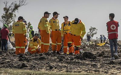 Members of Israel's Zaka rescue and recovery team Israel examine wreckage at the scene where the Ethiopian Airlines Boeing 737 Max 8 crashed shortly after takeoff killing all 157 on board, south of Addis Ababa, in Ethiopia on March 12, 2019. (AP Photo/Mulugeta Ayene)