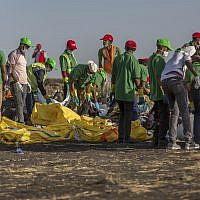 Workers collect clothes and other materials, under the instruction of investigators, at the scene where the Ethiopian Airlines Boeing 737 crashed shortly after takeoff killing all 157 on board, near Bishoftu, Ethiopia on March 12, 2019. (AP Photo/Mulugeta Ayene)