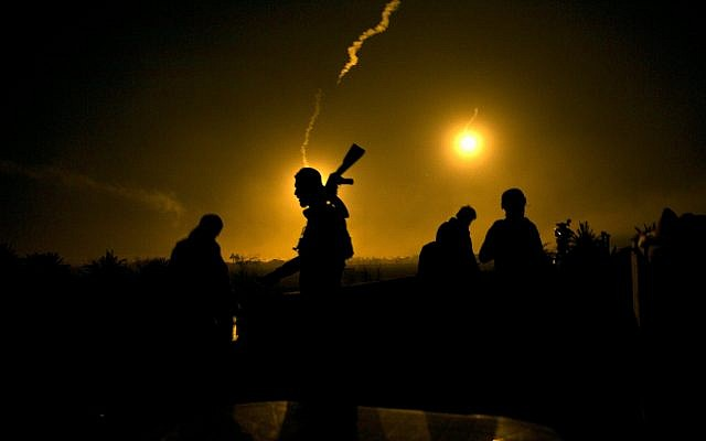 A US-backed Syrian Democratic Forces (SDF) fighter watches illumination rounds light up Baghouz, Syria, as the last pocket of Islamic State militants is attacked on March 12, 2019. (AP /Maya Alleruzzo)