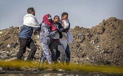 A grieving relative who lost his wife in the crash is helped by a member of security forces and others at the crash site of the Ethiopian Airlines Boeing 737 Max 8, March 13, 2019. (AP/Mulugeta Ayene)