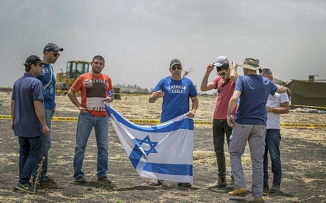 Israeli relatives hold the national flag at the crash site of an Ethiopian Airlines Boeing 737 Max 8, seen here on March 14, 2019. (Mulugeta Ayene/AP)