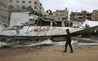 A Palestinian inspects the damage at the Hamas Prisoners Ministry after Israeli airstrike, Gaza City, March 15, 2019 (AP Photo/Adel Hana)