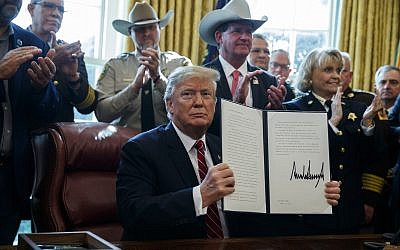US President Donald Trump signs the first veto of his presidency in the Oval Office of the White House, March 15, 2019, in Washington. (AP Photo/Evan Vucci)