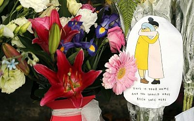 A message card is placed at a collection of flowers left at the Botanical Gardens in Christchurch, New Zealand, March 16, 2019. (Vincent Thian/AP)