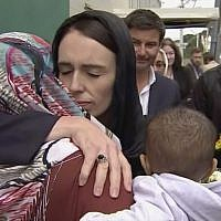 In this image made from video, New Zealand's Prime Minister Jacinda Ardern, center, hugs and consoles a woman as she visited Kilbirnie Mosque to lay flowers among tributes to Christchurch attack victims, in Wellington, March 17, 2019. (TVNZ via AP)