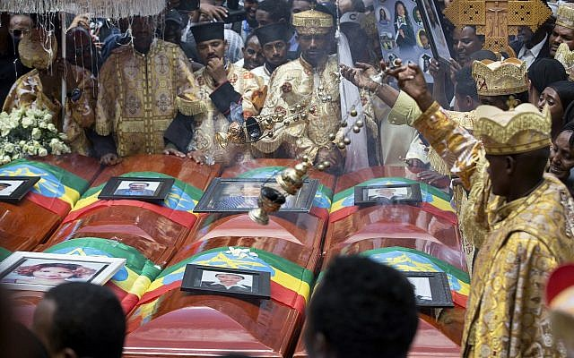 Priests swing incense over empty caskets draped with the national flag at a mass funeral at Holy Trinity Cathedral in Addis Ababa, March 17, 2019. Thousands of Ethiopians turned out to a mass funeral ceremony a week after the Ethiopian Airlines plane crash in which 157 people died. (AP Photo/Mulugeta Ayene)