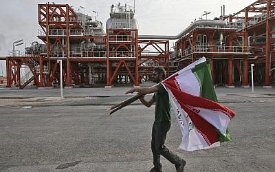 In this Saturday, March 16, 2019 photo, an Iranian worker carries Iranian flags prior to an inauguration ceremony of a natural gas refinery at the South Pars gas field on the northern coast of the Persian Gulf, in Asaluyeh, Iran. (AP/Vahid Salemi)
