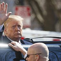 US President Donald Trump waves as he boards his motorcade vehicle after he and First Lady Melania Trump attend a service at Saint John's Church in Washington, DC, March 17, 2019. (AP Photo/Carolyn Kaster)