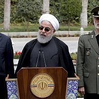 President Hassan Rouhani, center, speaks during a media briefing after a cabinet meeting, as senior Vice President Eshaq Jahangiri, left, and Defense Minister Gen. Amir Hatami listen, in Tehran, Iran, March 18, 2019. (Iranian Presidency Office via AP)