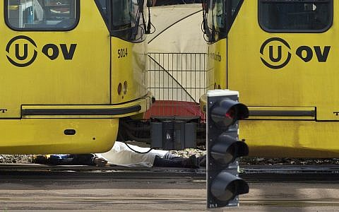 A body covered with a blanket next to a tram following a shooting in Utrecht, Netherlands, Monday, March 18, 2019. (AP Photo/Peter Dejong)