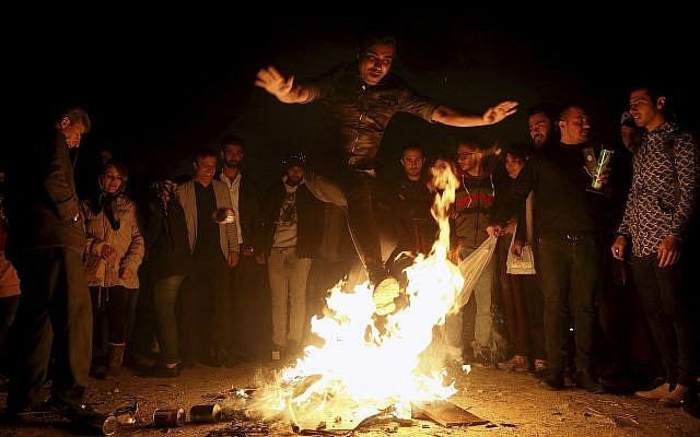 An Iranian man jumps over a bonfire March 19, 2019 in Tehran as Iranians observed a nearly 4,000-year-old Persian tradition known as the Festival of Fire. (AP/Ebrahim Noroozi)