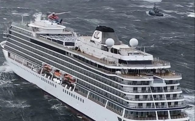 A rescue helicopter flies over the cruise ship Viking Sky evacuating 1,300 passengers and crew amid stormy seas after it sent out a mayday signal due to engine failure, March 23, 2019. (CHC helicopters via AP)
