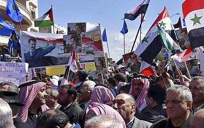 In this photo released by the Syrian official news agency SANA, Syrians hold national flags and portraits of Syrian President Bashar Assad during a protest against US President Donald Trump's move to recognize Israeli sovereignty over the Golan Heights, in Homs, Syria, on March 26, 2019. (SANA via AP)