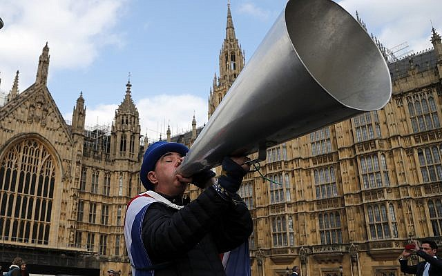 A pro EU protester shouts through a megaphone at the Houses of Parliament in London, Wednesday, March 27, 2019 as British lawmakers were preparing to vote on alternatives for leaving the European Union. (AP Photo/Frank Augstein)
