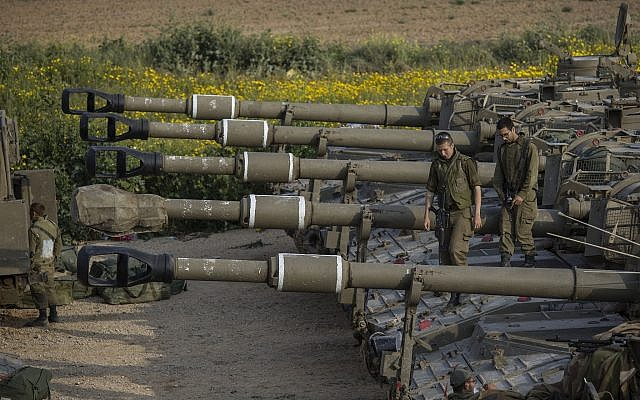 Israeli soldiers sit on top of mobile artillery near the border with the Gaza Strip, in southern Israel, March 27, 2019. (AP Photo/Tsafrir Abayov)
