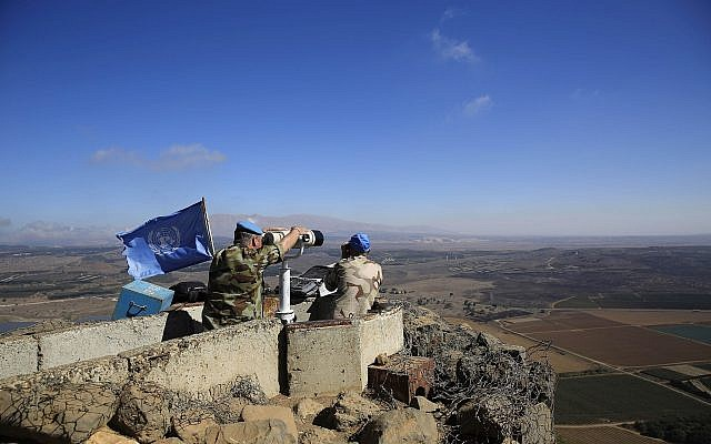 In this photo taken on Tuesday, Sept. 16, 2014, UN peacekeepers from the United Nations Disengagement Observer Force, also known as UNDOF, observe Syria's Quneitra province at an observation point on Mt. Bental in the Israeli-controlled Golan Heights, overlooking the border with Syria. .(AP Photo/Tsafrir Abayov)
