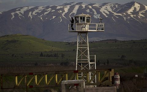 A UN peacekeeper from the UNDOF force stands guard on a watch tower at the Quneitra Crossing between Syria and the Israeli-controlled Golan Heights, Friday, March 8, 2013. (AP/Ariel Schalit)