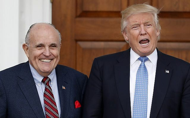 Then US President-elect Donald Trump calls out to media as he and former New York mayor Rudy Giuliani pose for photographs as Giuliani arrives at the Trump National Golf Club Bedminster clubhouse, November 20, 2016, in Bedminster, New Jersey. (AP Photo/Carolyn Kaster)