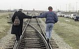 A couple holds hands as they walk balanced on the rails of the railroad tracks that brought more than a million people to their deaths at the Auschwitz-Birkenau concentration camp on January 26, 1995. (AP/Jockel Finck)