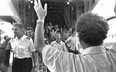 Israeli Foreign Minister Yigal Allon (back to camera) welcoming the rescued Air France passengers and crew including pilot Michel Bacos (left) coming off an Israel Air Force Hercules plane at Ben Gurion Airport, July, 1976 (Moshe Milner, Israel Government Press Office)